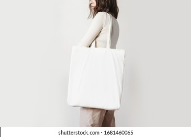 Urban mockup of tote bag. Girl holding white cotton tote bag on a white wall background. Template can be used for you design