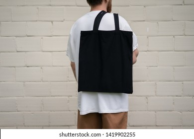 Urban mockup of tote bag. Men holding black cotton tote bag on a brick wall background. Template can be used for you design