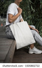 Urban mockup of tote bag. Woman holding white cotton tote bag on a nature background. Template can be used for you design