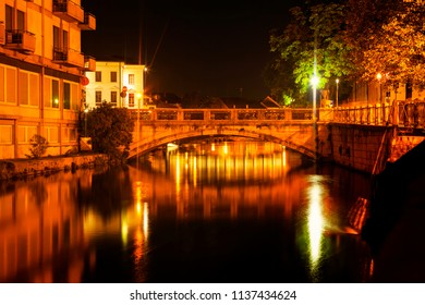 Urban night scene with bridge and flowing river