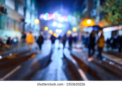Urban night scene with people walking out of focus with colored background.