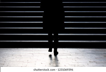 Urban night walk : Blurry silhouette of young woman climbing up the city street public stairs in the peaceful winter moonlight , alone, from behind