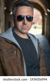 Urban outdoor portrait of a handsome mature man wearing brown jacket with sunglasses, street style at spring