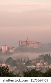 Urban Photography. Morning sunlight/sunrise in the city Zlin, Czech Republic, Europe with fog presenting misty mood of the location. Cloudy color sky as a background.