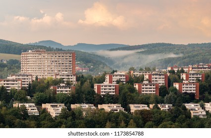 Urban photography of typical residential buildings of inhabitans in the city Zlin, Czech Republic, Europe. Beautiful green trees, fogy hills and colorful sky make a nice image of this Bata town.