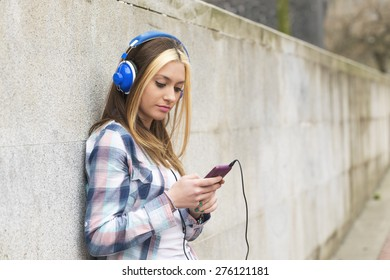 Urban portrait beautiful girl with headphones and smart phone listening music in the street.
