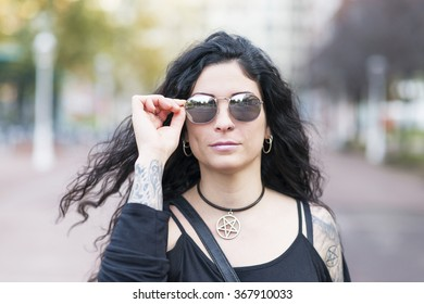 Urban portrait of beautiful woman with sunglasses heavy metal style.