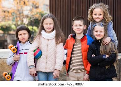Urban portrait of little school girls and boys in jackets