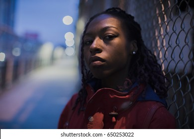 Urban portrait of a young, black woman in the streets of New York City. The model poses on the city's Manhattan Bridge.