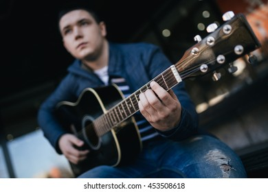 Urban portrait of young musician playing guitar. Teenager lifestyle.