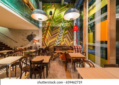 Urban restaurant interior with green plants on the wall in the evening