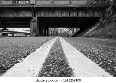 Urban road with bridge overpass. Black asphalt pavement street road with yellow road markings. Abstract street urban street photography.