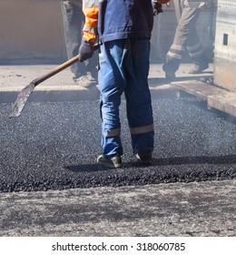 Urban road under construction, asphalting in progress, worker with a shovel in blue uniform