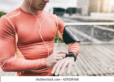 Urban runner man looking app on sportwatch. Male running jogging smart watch outside