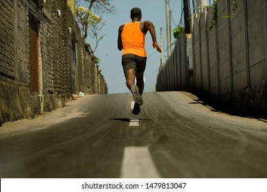 urban runner workout . Back view of athletic black African American professional sport man running training hard outdoors on asphalt road during jogging workout in healthy lifestyle