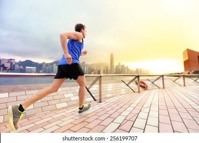 Urban running man runner in Hong Kong city skyline. Caucasian man working out jogging on the promenade of Victoria Harbor in HongKong, China, in afternoon sunset during spring.