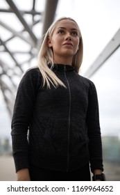 Urban scandinavian woman in workout outfit standing on a bridge