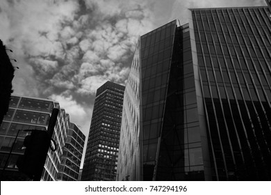 Urban scene of city skyline with glass tower blocks or offices with moody cloudy sky.