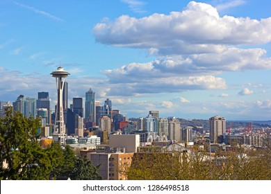 Urban Seattle panorama and distinctive peak of Mount Rainier above the clouds on horizon. Scenic view on urban skyline from a high elevation point in Seattle, USA.