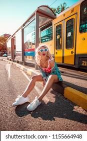 Urban shot of beautiful blonde girl, sitting