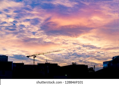 Urban skyiline in silhouette with heavy colorful clouds overhead and construction crane above buildings as city of Christchurch redevelops post earthquake