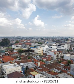 The urban skyline of the densely populated Bandung city in Java Island, Indonesia, against a blue cloudy sky.
