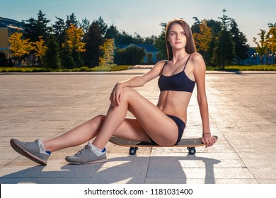 Urban sport concept. Sporty woman is sitting on skateboard and looking up