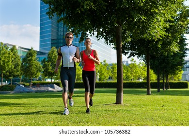 Urban sports - couple jogging for fitness in the city on a beautiful summer day