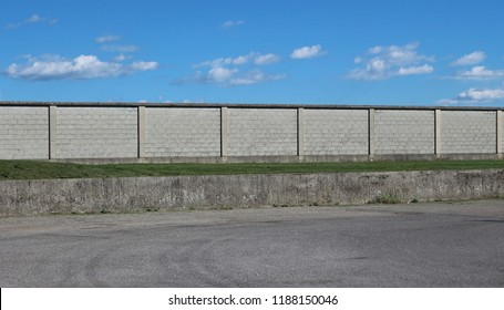 Urban street background. Am asphalt road in front of a long concrete brick wall under a blue sky with fluffy clouds