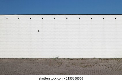 Urban street background. Concrete road, a white wall  made of square bricks and blue sky
