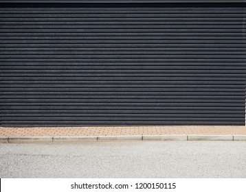 Urban street background for copy space. A black concrete wall with horizontal stripes, a brown tile sidewalk and an asphalt road in front of it