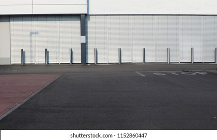 Urban street background. An intersection of streets in front of a modern white building with a row of metal street poles. No people.