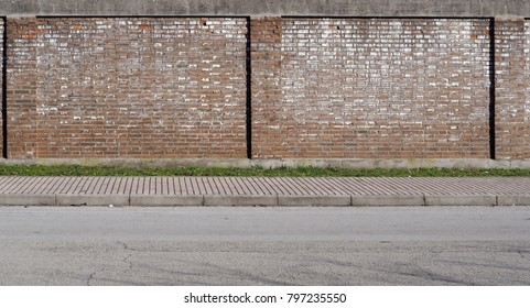 Urban street background. Old brick wall, a line of grass, a large sidewalk and an asphalt road