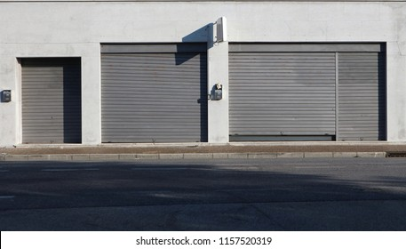 Urban street background. Shop retail with metal shutters closed on the sidewalk at the side of the road.