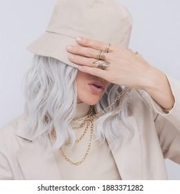 Städtische Straße Stil Blonde. Details des täglichen Aussehens. Beigefarbenes Outfit und Accessoires. Eimerhut und Ringe. Trendminimalistische Mode