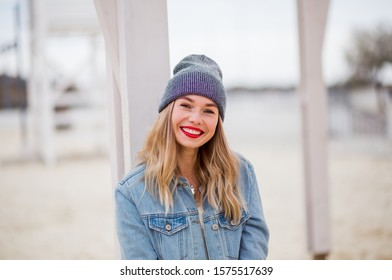 Urban style blond woman wearing hat and jeans jacket with red lips and beautiful white smile. Girl walk on the beach. Space for text.