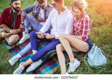 Urban style multicultural tourists having fun outdoors, wearing summer casual clothes, sitting on checkered rug in park area - Concepts of youth and togetherness and outdoor recreation pursuit