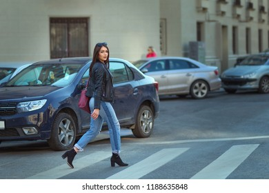 Urban style: Stylish beautiful woman crossing the street wearing black leather jacket and boyfriend jeans. Beautiful model in autumn or spring clothes.