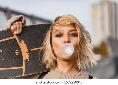 Urban stylish young girl walking with skateboard. Outdoors portrait of active sport woman model. Healthy lifestyle. Extreme sports. Close up portrait of a pretty young girl chewing bubble gum.