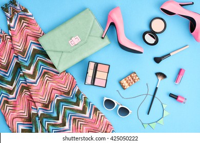 Urban summer girl colorful outfit. Fashion stylish clothes, cosmetics, makeup accessories. Glamor heels, handbag clutch, trendy pants, sunglasses. Woman essentials