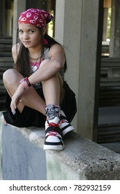 Urban teen wearing a pink bandana, sitting with feet crossed on a concrete wall, looking straight ahead. She could be a gang member, runaway, or juvenile delinquent looking for trouble.