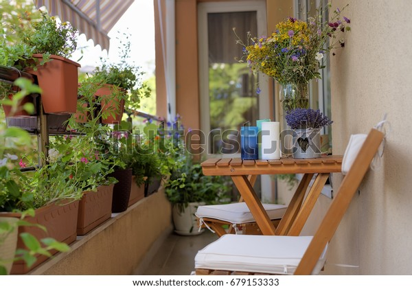 Urban terrace with flowers. Table with a bouquet of wildflowers, lavender and scented candles. Dining relaxation and recreation.