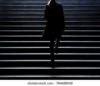 Urban walk : Blurry silhouette of young elegant woman climbing up the city street public stairs in the winter, alone , from behind