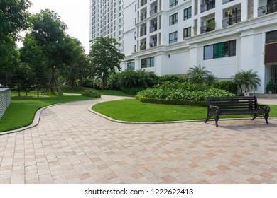 Urban walking road among green tree in modern apartment buildings in big city.