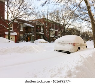 Urban winter street with cars stuck in snow. Montreal, Quebec, Canada.