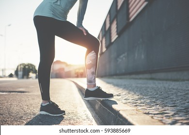 Urban woman athlete standing on the city street. Sport tight clothes. Resting after hard workout