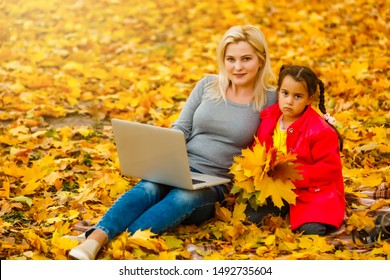 Urban woman and daughter with laptop in park. slim hipster woman in jeans using notebook. freelancer using communication technology remote work and eco-friendly lifestyle.