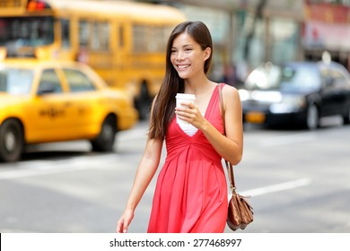 Urban woman drinking coffee happy smiling in New York City, Manhattan. Girl drinking hot drink from disposable cup walking in street wearing red dress. Biracial Asian Caucasian female model.