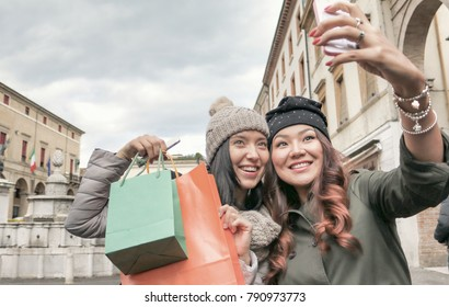 urban women shopping and having fun together. two girls with shopping bags smiling and taking photo with mobile phone. asian and european friends of diversity.