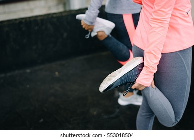 Urban workout and running concept. Women stretching legs for warming up before exercising.